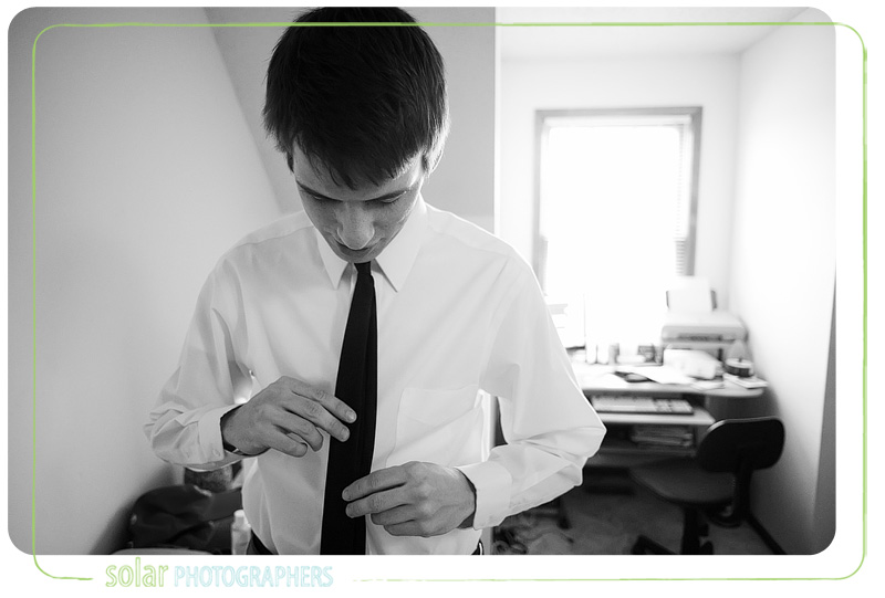 A groom fixing his tie.