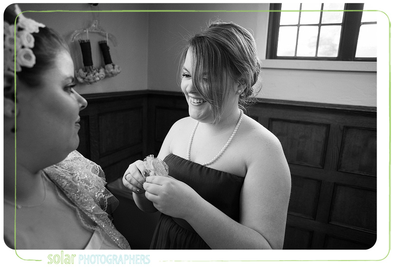 A bride's sister helps put finishing touches on her dress.