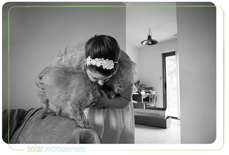 A bride hugs her dog.