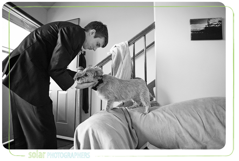 A groom hugs his dog.