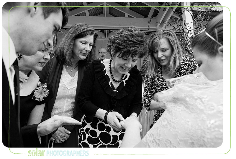 Women checking out bride's wedding ring.