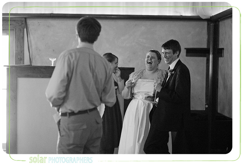 Bride and groom laughing at best man's speech.