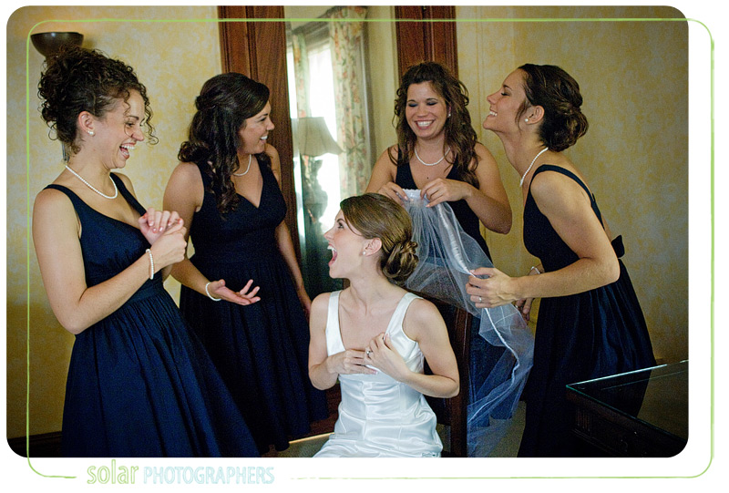 A bride laughing with her bridesmaids at Loose Mansion in Kansas City, MO.