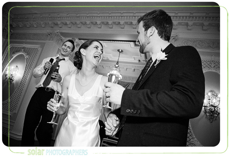 A bride laughs at her groom during the best man's speech at Loose Mansion.