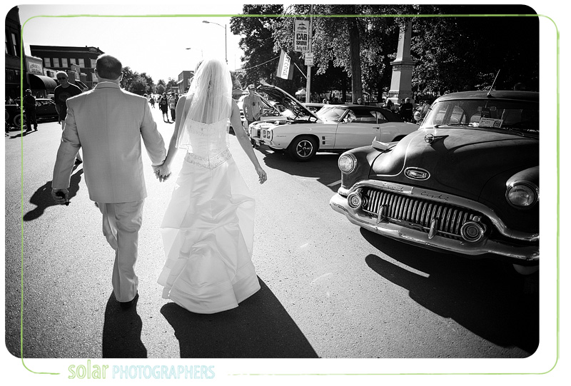 a bride and groom holding hands walking down the street.