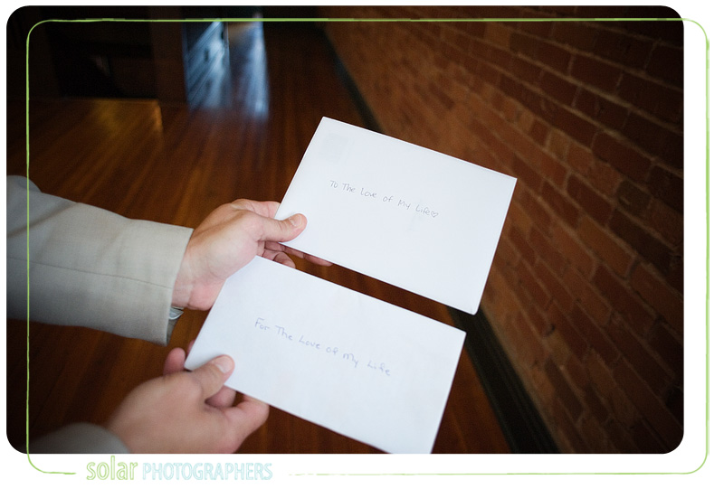 a groom holding two cards with the same writing.