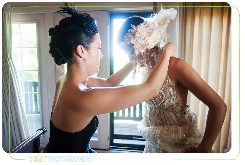 Bridesmaid helps get bride dressed for her wedding.
