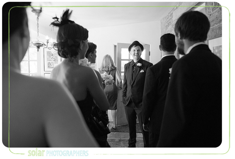 Groom laughs with wedding party before his gorgeous Lawrence wedding.