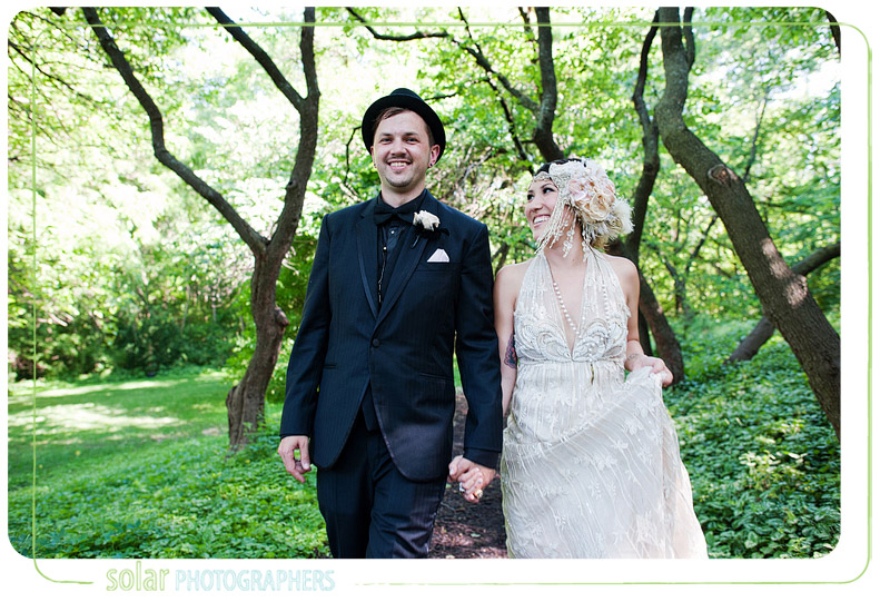 Beautiful portrait of a bride and groom walking down a tree lined path at the Evan Williams House in Lawrence Kansas.