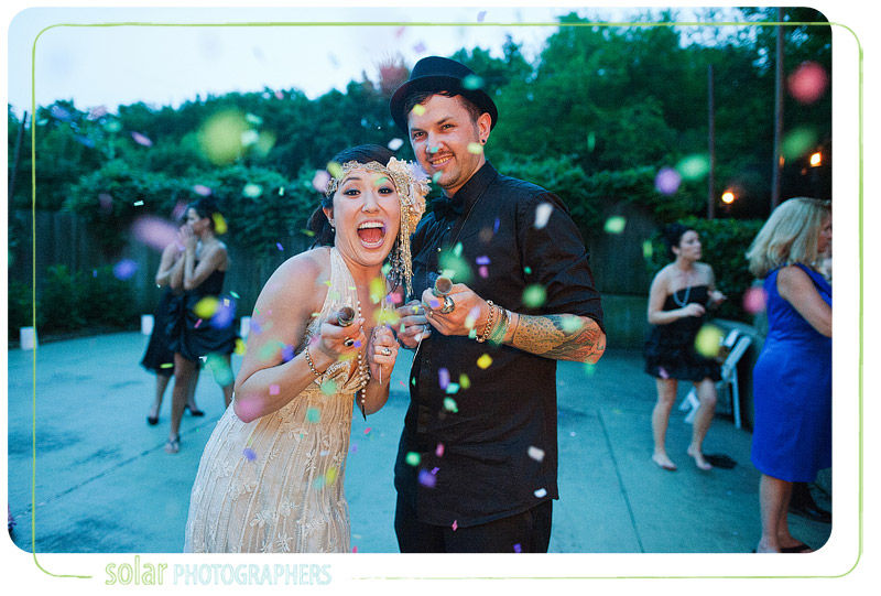 Awesome picture of the Bride and groom shooting confetti at their wedding in Lawrence, KS.