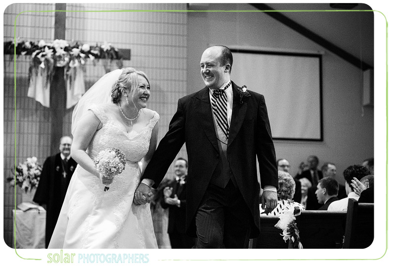 Bride and Groom smile as they walk back down the aisle of their Kansas City wedding.