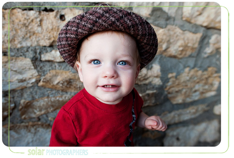 A little boy smiling in a cute hat.