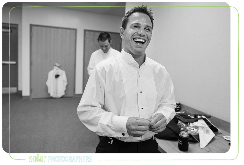Groom candidly laughing at his groomsmen.