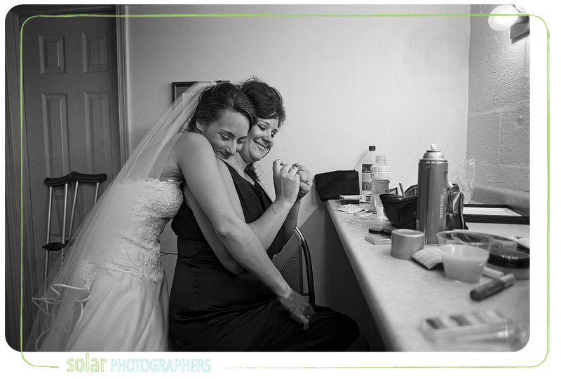 Bride sharing an emotional moment with a bridesmaid before her Kansas City wedding.