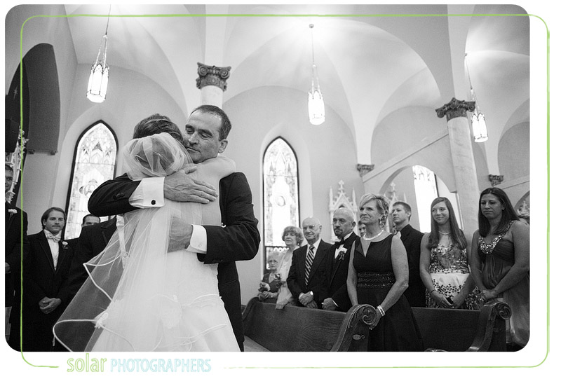 Father and his bride share an emotional hug during a wedding ceremony.