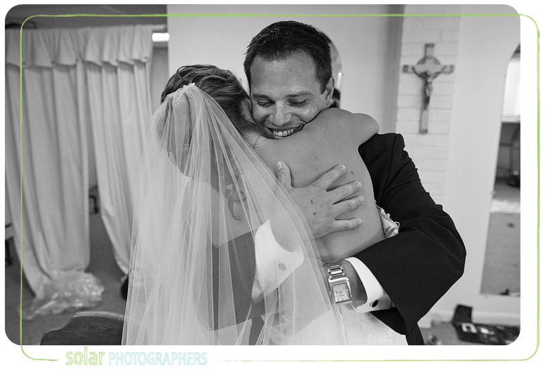 An excited bride and groom embrace after their wedding.