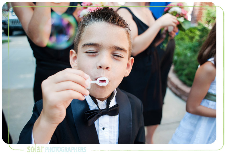 A little boy blowing bubbles at a wedding.