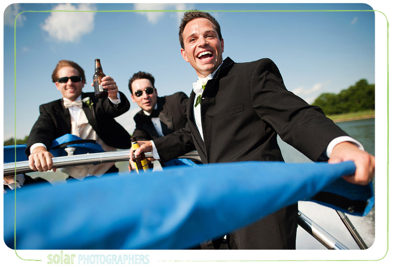 Groom laughing as his hair blows in the wind on a boat in Kansas City.