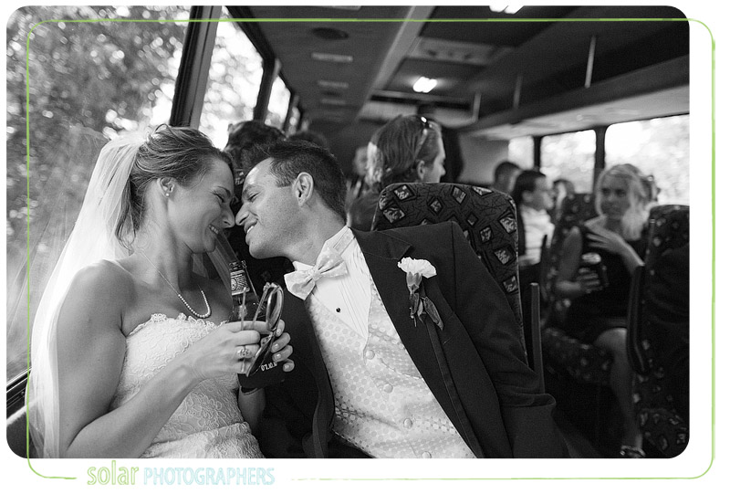 Bride and groom snuggle on a bus.