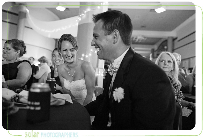 Bride and groom laughing during the toasts at their reception.