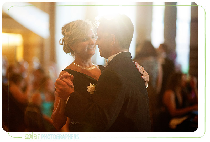 A mother and son share a dance at a wedding reception.