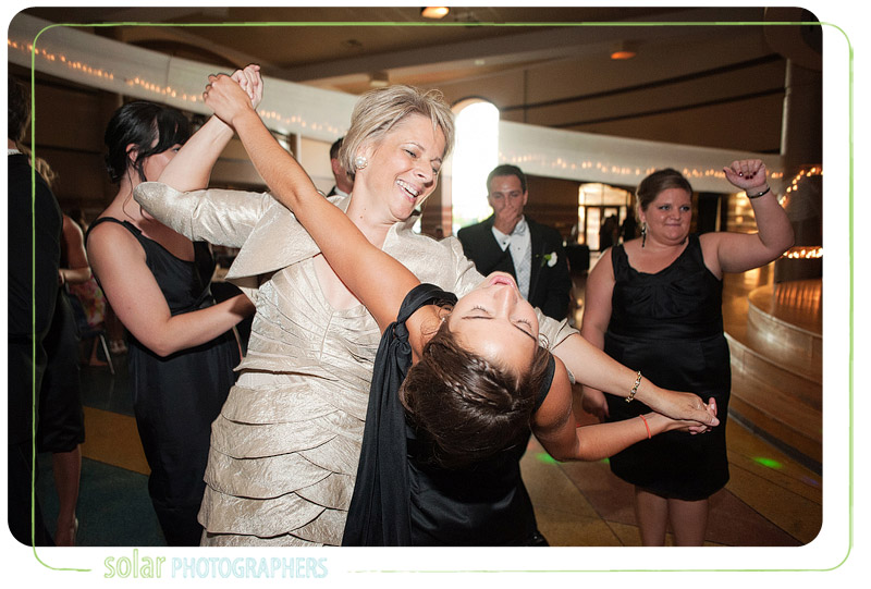 A mother dances with her daughter at a fun wedding reception.