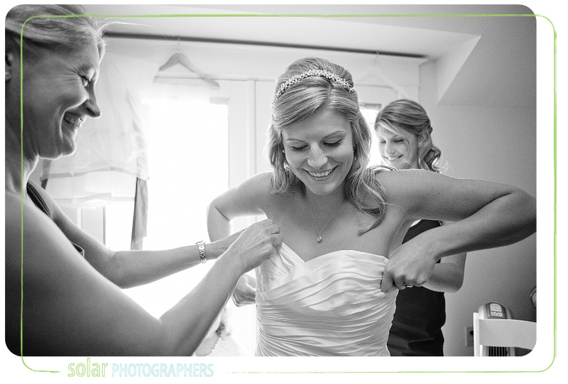 Bride getting her wedding dress on with the help from her mom and sister.