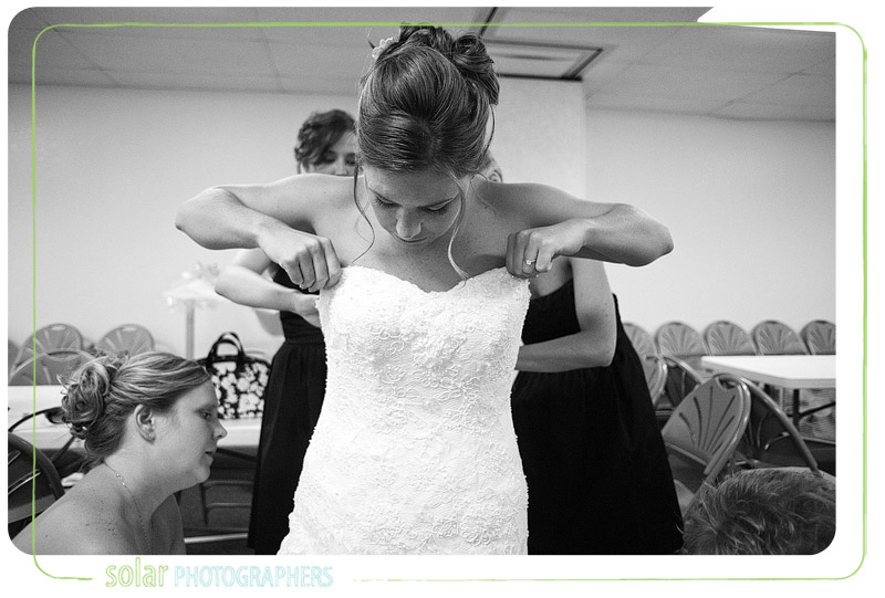 Bride putting on her wedding dress.