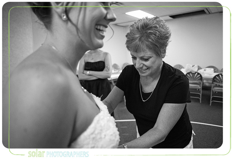 Mom lacing up the bride on her wedding day.