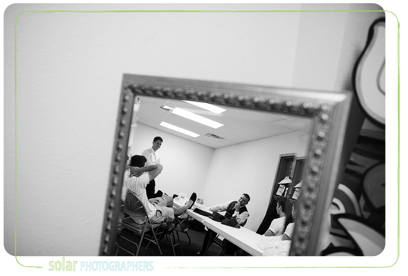 Shot of a mirror with groom laughing with his friends.