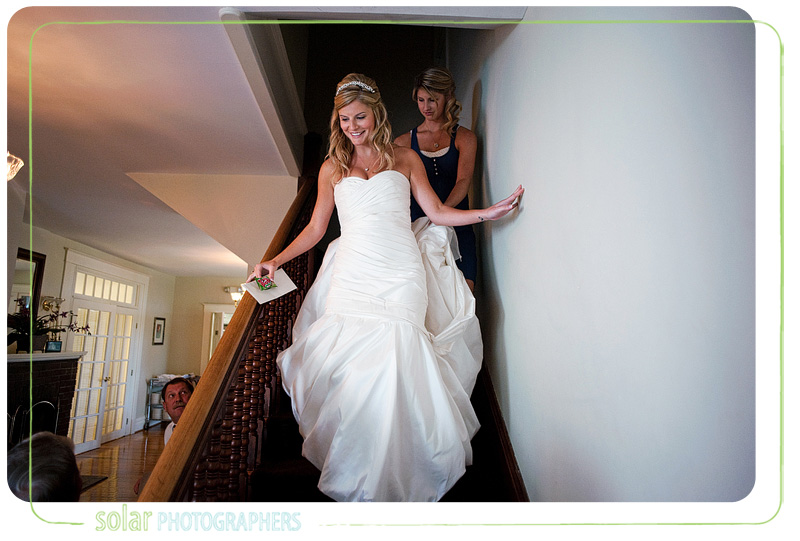 Bride walks down the stairs smiling.