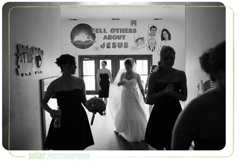 Bride walks down the hall with her bridesmaids before her wedding.