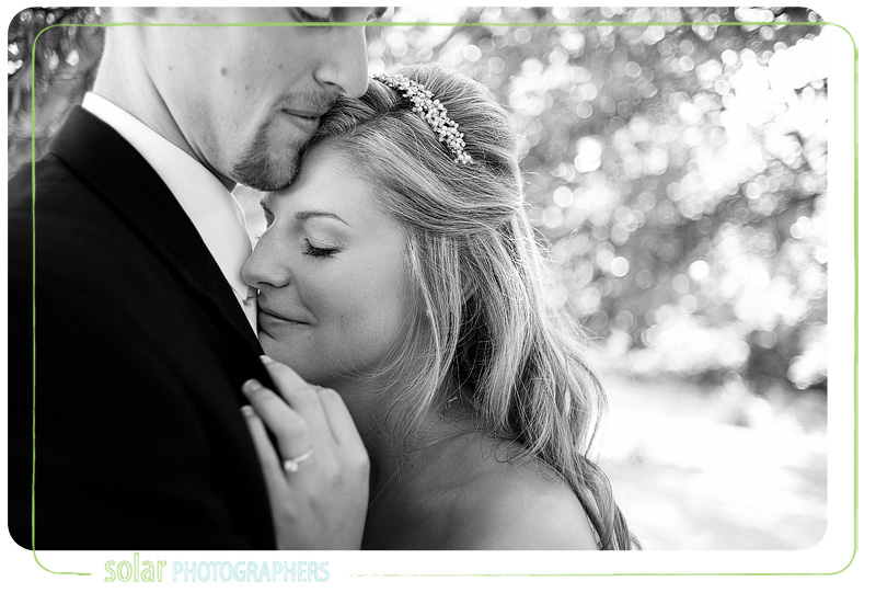 Bride holds her husband and smiles because she loves him a lot.