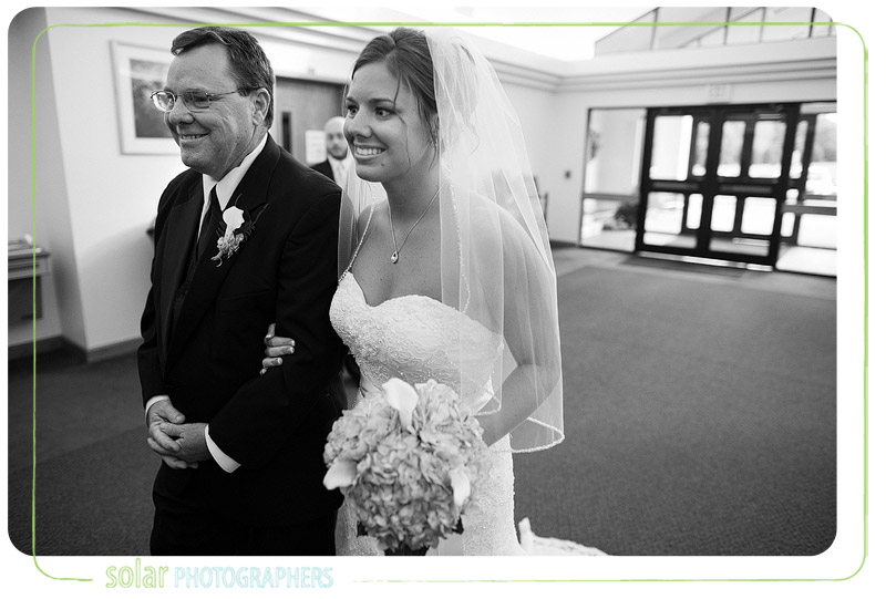 Bride and her father smiling as they get ready to walk down the aisle.