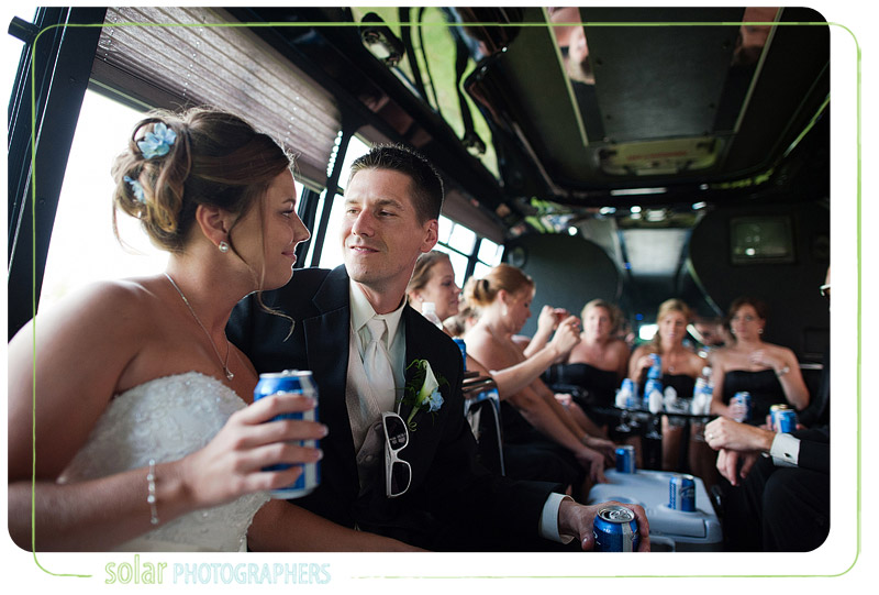 Groom looks at his wife with lots of love on their party bus.
