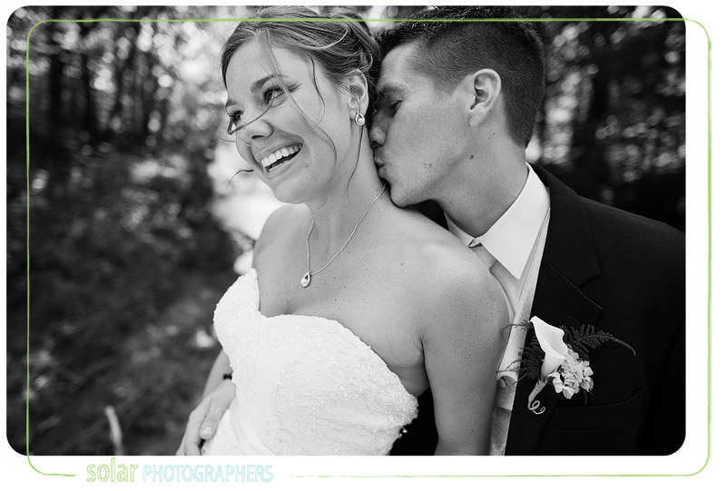 Groom kisses his wife on the neck and she laughs.