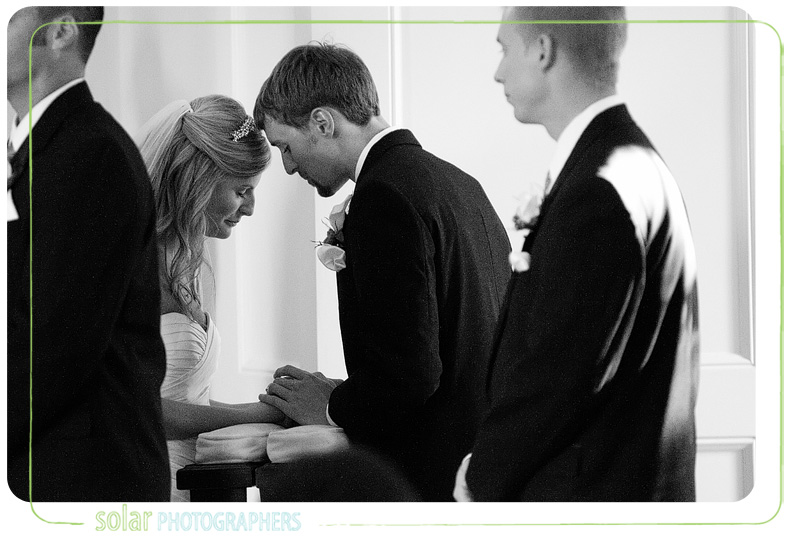 Couple prays together during their wedding at the Hawthorne House in Kansas City.