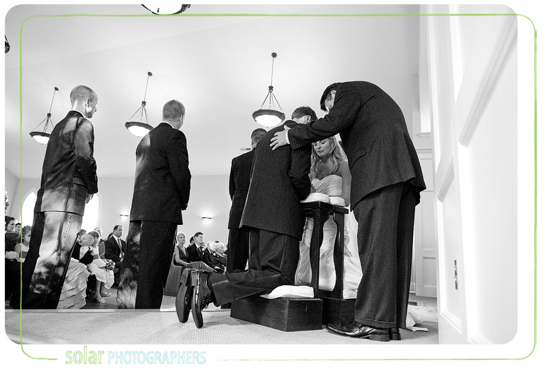 A wide shot of the bride and groom praying together during their wedding.