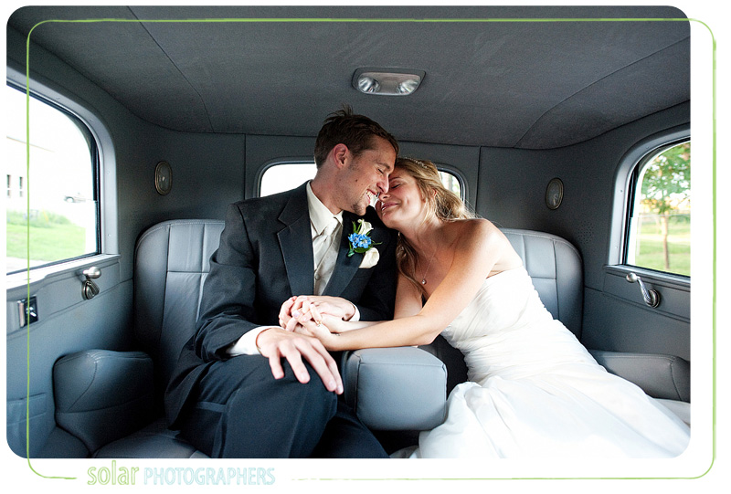 Couple snuggles in the limo after their wedding ceremony.