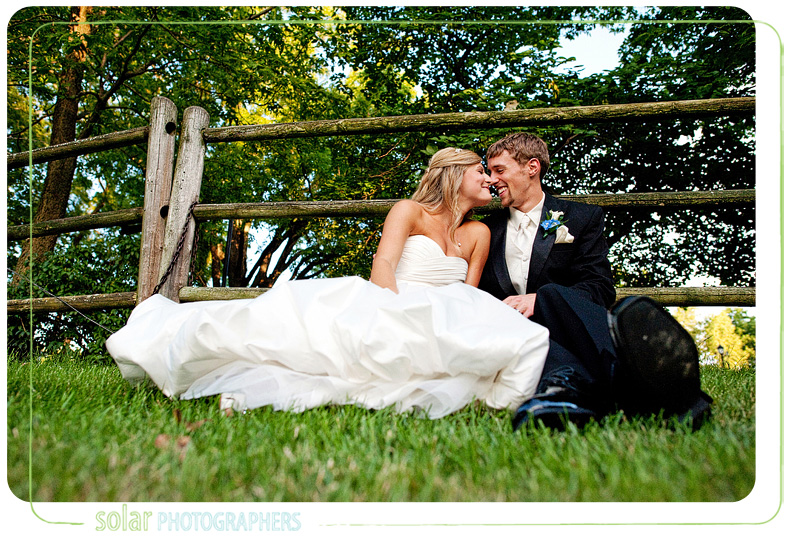 Beautiful portrait of a couple sitting in the grass on their wedding day.