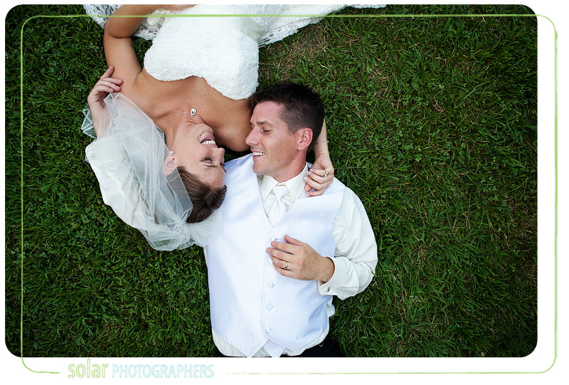 Bride and groom lay in the grass together on their wedding day.