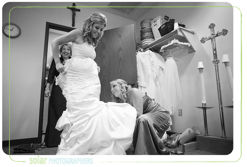 Bride putting on her beautiful wedding dress.
