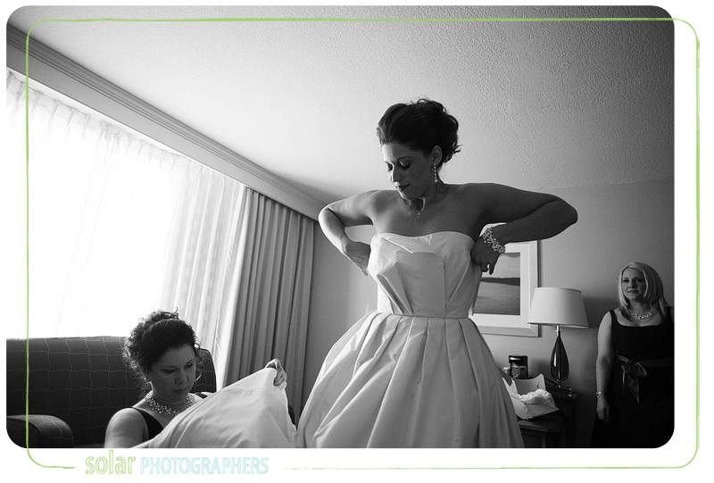 Bride putting her beautiful wedding gown on.
