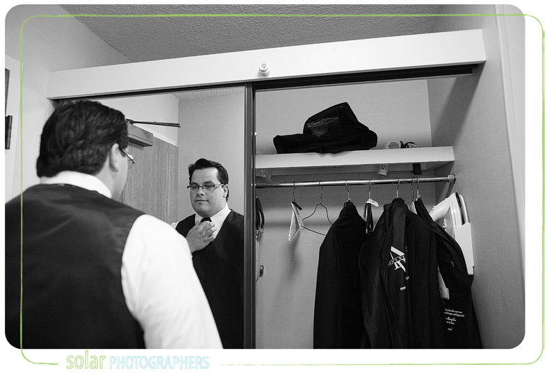 Groom adjusts his tie in a mirror.