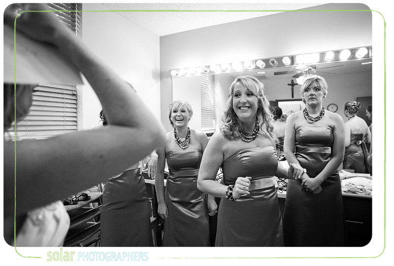 Bridesmaids smile at bride after she puts on her gorgeous wedding dress.