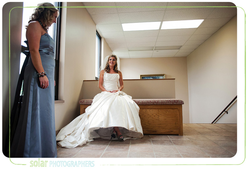 Bride and her sister wait anxiously for groom to arrive for their first moment on their wedding day.
