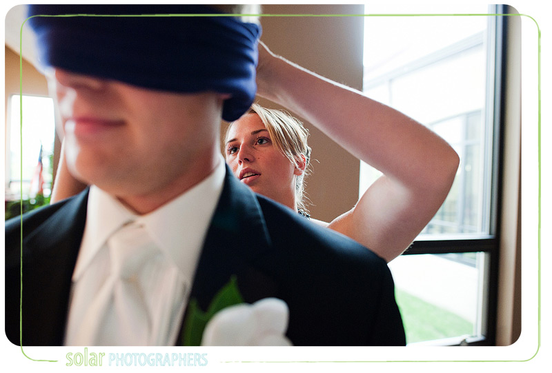Groom getting blindfold on.