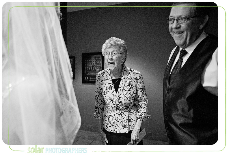 Grandma and father of the bride look at bride with huge smiles.