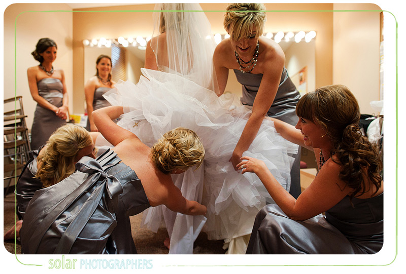 Bridesmaids fluff the bride's wedding dress.