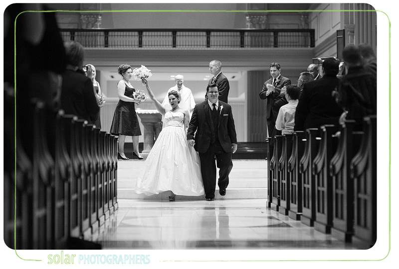 Excited bride walks down the aisle after getting married.